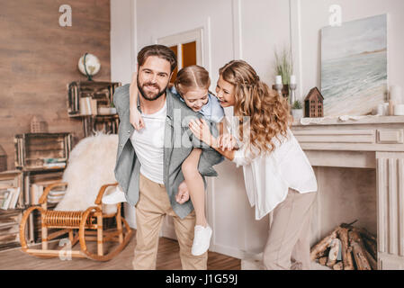 Father piggybacking happy daughter. Family having fun at home - Stock Photo