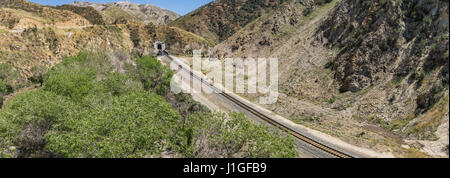 Railroad track leads through desert to mountain tunnel in California hills. - Stock Photo