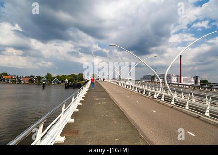 ZAANDAM, NETHERLANDS - JULY 4, 2016 : View of stone bridge on cloudy sky. Zaanse Schans is popular with windmills. - Stock Photo