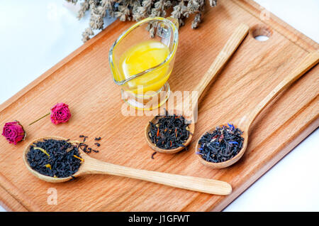 Black tea with herbs in wooden spoons with a glass container with honey on a wooden board decorated flowers of rose - Stock Photo