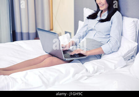 smiling businesswoman with laptop typing in bed - Stock Photo
