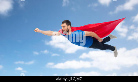 Superhero flying in the sky over night city retro poster style man in red superhero cape flying over blue sky stock photo publicscrutiny Images