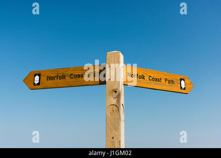 A signpost giving directions on the Norfolk Coast Path, a long distance footpath around the coast of Norfolk UK - Stock Photo