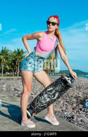 Fashion pretty blonde girl wearing sunglasses with skateboard stand against sea and palm. Female doing active sport - Stock Photo