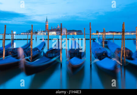 Gondolas moored along waterfront of Saint Mark's Square with church of San Giorgio Maggiore in background - Stock Photo