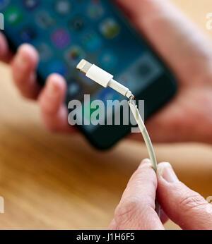 Broken iPhone charging lead - Stock Photo