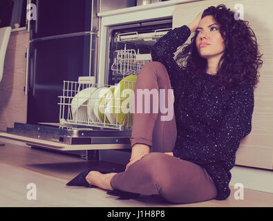 Stressed woman relaxing in the kitchen sitting on a floor - Stock Photo