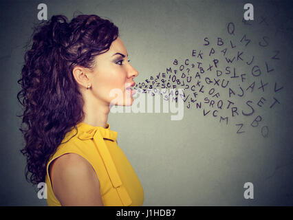 Woman talking with alphabet letters coming out of her mouth. Communication, information, intelligence concept - Stock Photo
