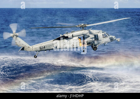 Navy Officer prepares to jump from an MH-60S Seahawk during search and rescue training - Stock Photo