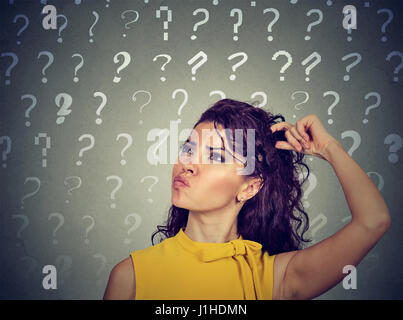 Portrait confused thinking young woman bewildered scratching her head seeks a solution looking up at many question - Stock Photo