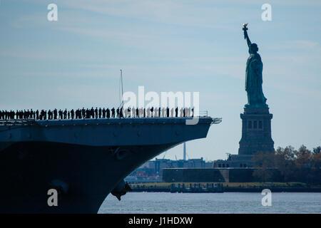 USS Iwo Jima (LHD 7) sails past the Statue of Liberty as it enters New York Harbor, USA - Stock Photo