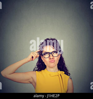 Confused skeptical woman thinking looking up isolated on gray wall background with copy space above head. Human - Stock Photo