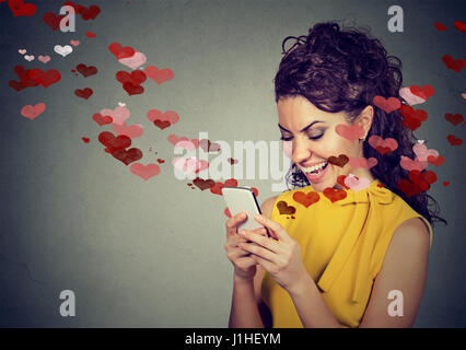 Beautiful happy woman sending love text message on mobile phone with red hearts flying away from screen isolated - Stock Photo