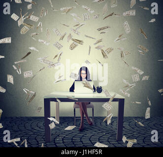 Young woman working on a laptop building online business making money cash falling down. Beginner IT entrepreneur - Stock Photo