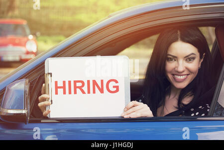 Happy woman sitting inside new car showing white card with hiring sign message on a dealership lot background - Stock Photo