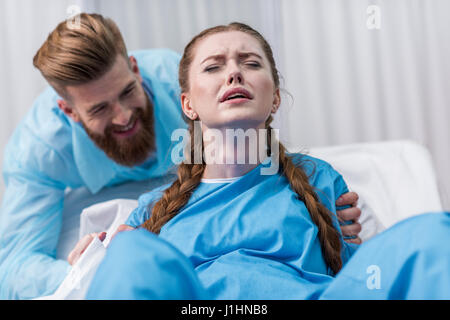 pregnant woman giving birth in hospital while man hugging her - Stock Photo