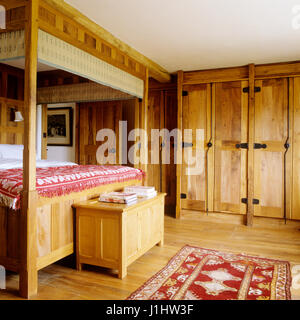 Four poster bed in country style bedroom. - Stock Photo