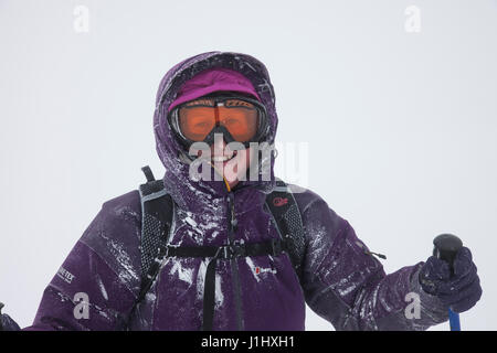 Smiling Middle Aged Woman Wearing Outdoor Equipment and Enjoying Winter Weather Conditions in the Mountains of Cumbria - Stock Photo