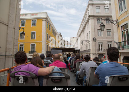 Tourists ride an open top bus in Lisbon, Portugal. - Stock Photo