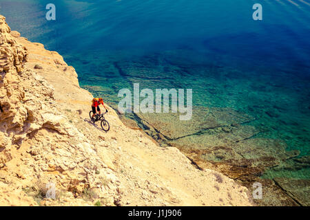 Mountain biker riding on bike in summer inspirational mountains and sea landscape. Man cycling MTB on enduro trail - Stock Photo
