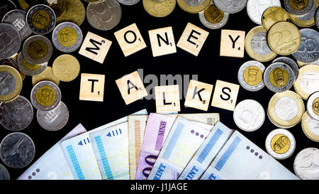 Budapest. Hungary, 21st of April 2017 - Scrabble pieces and money - coins and paper- in front of black background - Stock Photo