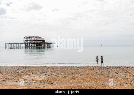 Day view of two women over Brighton Pier after fire. - Stock Photo