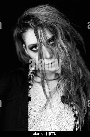 Close-up portrait of the sad lovely grunge (rock) girl. Black and white - Stock Photo