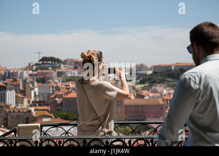 A lady taking a photograph of the city of Lisbon from a viewing terrace at the Barrio Alto in Portugal. - Stock Photo