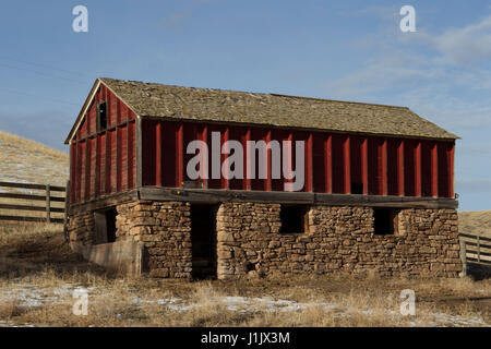 Old red granary. Fading paint, missing shingles, general disrepair give character to exposed frame and stone building. - Stock Photo