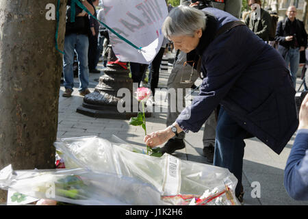 Paris, France. 21st April 2017. A mwoan lays flowers at the makeshift memorial. The day after the ISIS shooting - Stock Photo