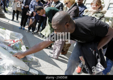 Paris, France. 21st Apr, 2017. A man lays flowers at the makeshift memorial. The day after the ISIS shooting at - Stock Photo