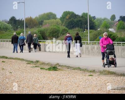Weymouth, Dorset, UK. 22nd Apr, 2017. People walking along the promenade on a overcast but bright day with a temperature - Stock Photo