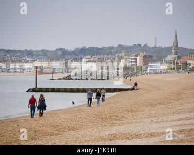 Weymouth, Dorset, UK. 22nd Apr, 2017. People walking along the beach on a overcast but bright day with a temperature - Stock Photo