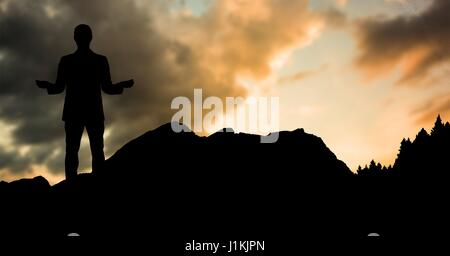 Digital composite of Silhouette businessman standing on hill against sky during sunset - Stock Photo