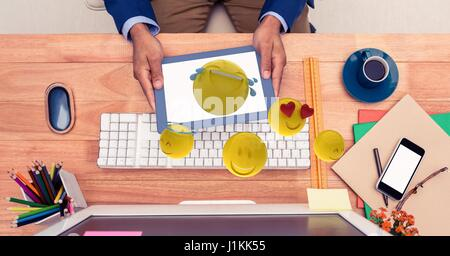 Digital composite of Emojis coming out of tablet PC held by businessman - Stock Photo