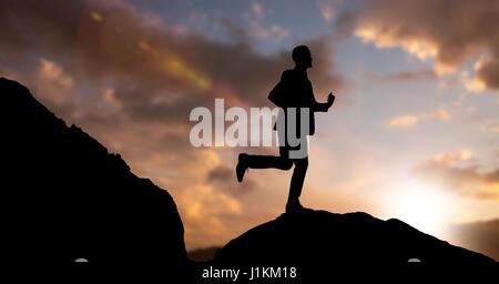 Digital composite of Silhouette businessman running on mountain against sky during dusk - Stock Photo