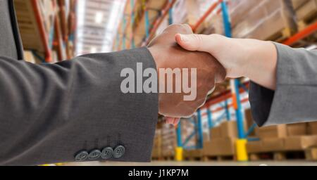 Digital composite of Male and female business partners shaking hands in warehouse - Stock Photo