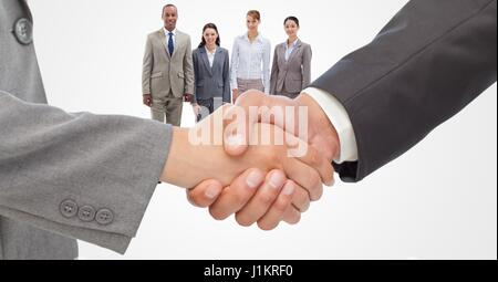Digital composite of Cropped image of businessmen doing handshake with employees in background - Stock Photo