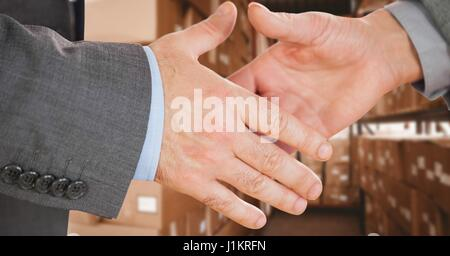 Digital composite of Business executives shaking hands in warehouse - Stock Photo
