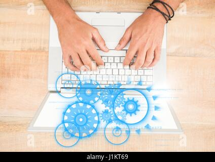 Digital composite of Overhead of hands on laptop with blue cog graphics - Stock Photo