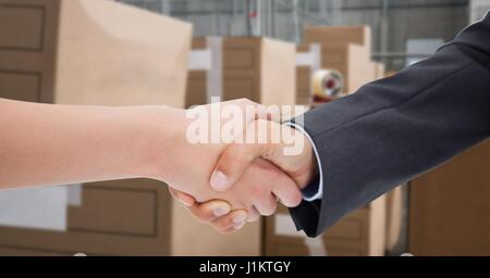 Digital composite of Cropped image of business people doing handshake in warehouse - Stock Photo
