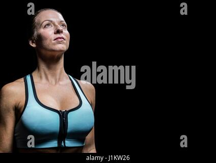Digital composite of Female athlete looking up against black background - Stock Photo