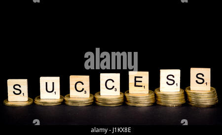 Budapest. Hungary, 21st of April 2017 - Scrabble pieces and coins in front of black background - concept of success - Stock Photo