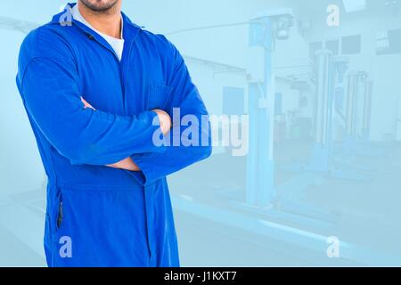 Digital composite of Midsection of worker with arms crossed standing in workshop - Stock Photo