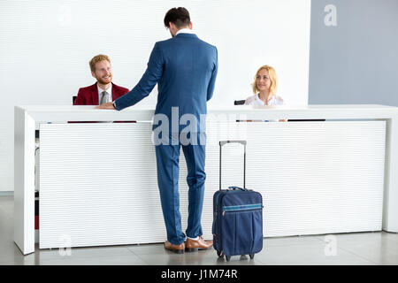 Kind female receptionist wish welcome to guest - Stock Photo