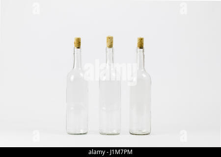 Three empty glass bottle with cork isolated on white background - Stock Photo