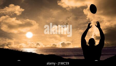 Digital composite of Silhouette player throwing rugby ball against sea during sunset