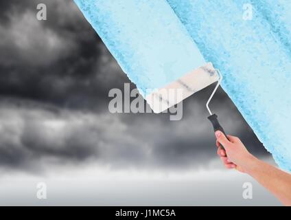 Digital composite of Hand with roller painting the sky - Stock Photo