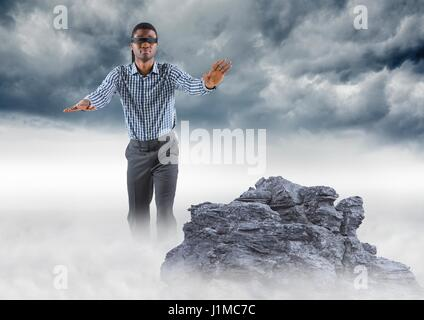 Digital composite of Business man blindfolded on misty mountain peak against storm clouds - Stock Photo