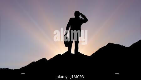 Digital composite of Silhouette businessman standing on mountain against sky during sunset - Stock Photo
